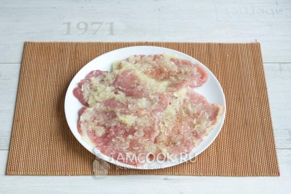 Обмазать мясо смесью лука и чеснока